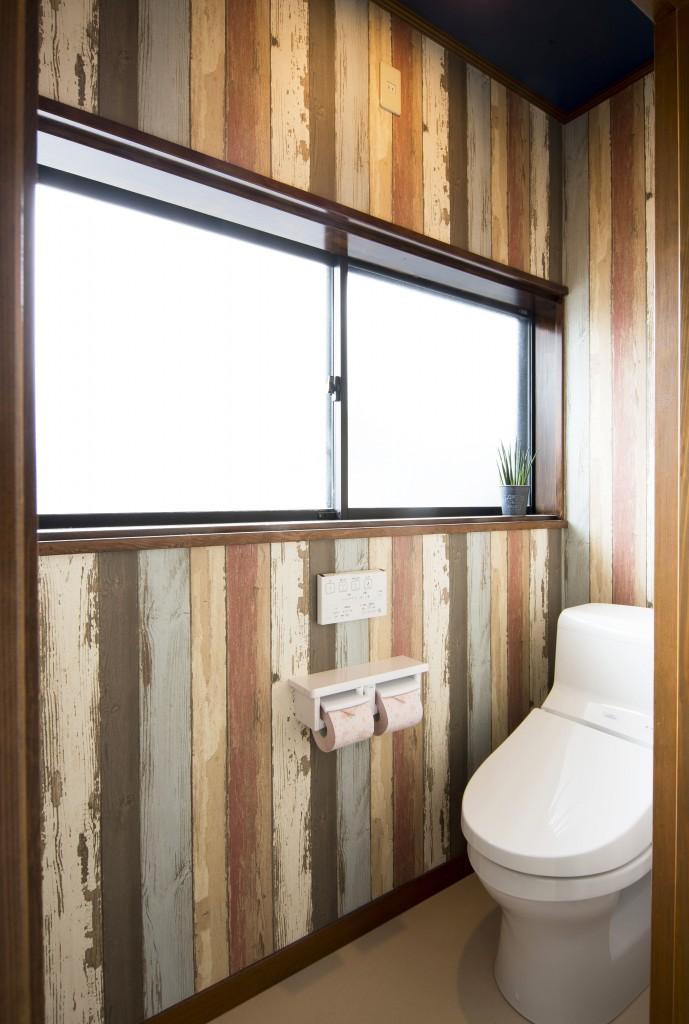 【仕様】トイレ…TOTO HVシリーズ 色:ホワイト カラフルな木目をアートしたポップなデザインのクロスを張り、メンズライクな空間に。天井は濃いブルーのクロスで空間を引き締めています。