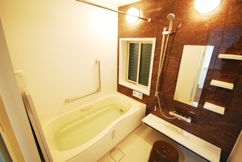 【仕様】LIXIL アライズ LBE 1620 アクセント:デオブローストーン/ベース:ホワイト/浴槽:ベージュ 浴室にはランドリーパイプを取り付けおもちゃなども引っ掛けておけるようにしました。まだお子様が小さなH様邸では大活躍だそうです。お祖母様にも安心してご入浴いただけるように手すりを取り付け安全性も確保しました。