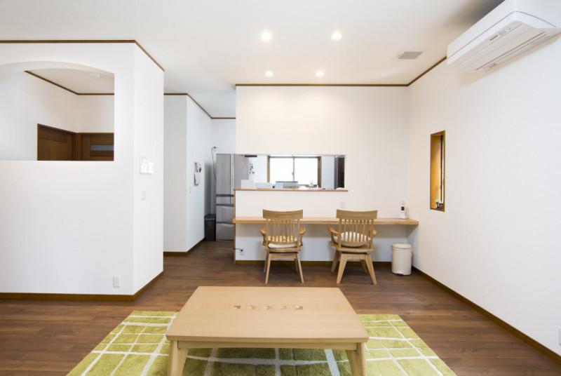既存の台所と居間と廊下をつないでLDK空間を広くとり、ダウンライトを使って明るい空間にしました。左側にはパソコンスペースを作り、リビングから見た時に圧迫感を感じないようにアーチ型にくり抜き開放感を出しました。