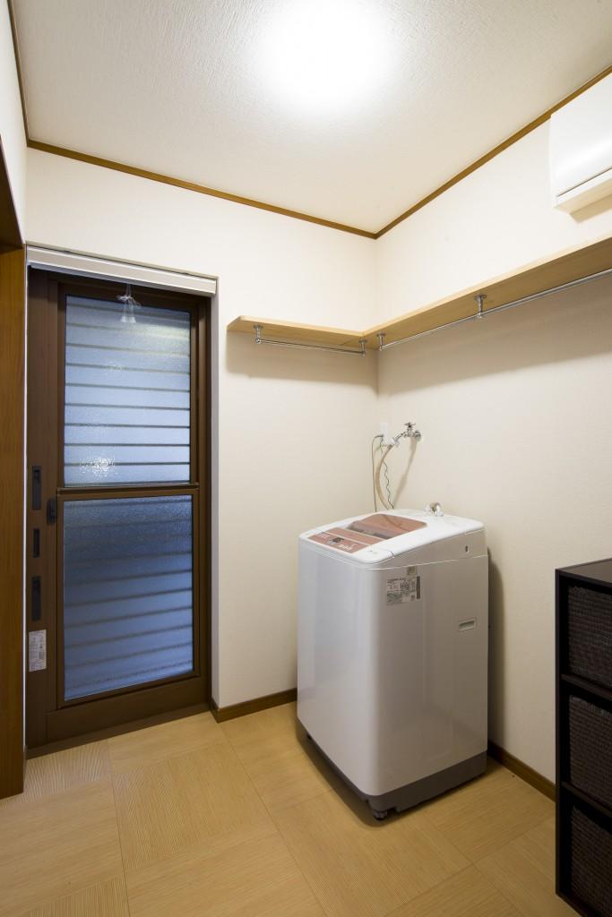 洗面脱衣室からは裏の車庫へと繋がっています。 磨りガラスとはいえ、着替えもされる場所ですので、ロールスクリーンを取り付け目隠しできるようにしました。ご用意いただいた木材を棚板として取り付け、収納力もアップ。